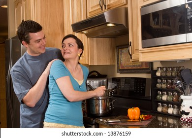 Happy couple in the kitchen. She is cooking on the stove near a counter and a chopped pepper. They are smiling as they look at each other happily. Horizontally framed photograph