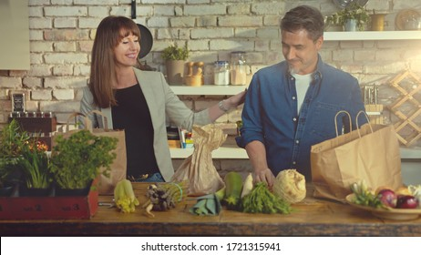 Happy couple in the kitchen unpacking grocery bags full of vegetables arriving home from shopping.