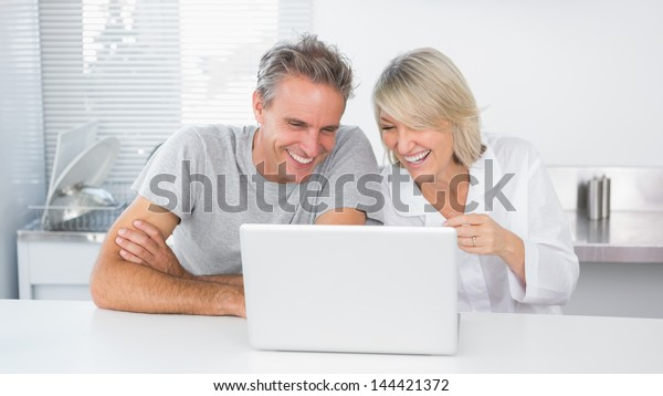 Happy couple laughing at laptop in the morning sitting at kitchen counter