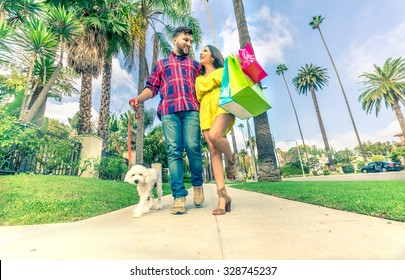 Happy couple laughing and walking while shopping - Boyfriend with poodle embracing his beautiful girlfriend walking on Beverly Hills - Rich persons having fun