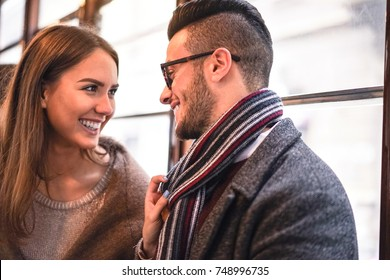 Happy couple laughing while looking each other in the bus - Young beautiful woman pulling her boyfriend by scarf next to her - Love, romantic, relationship concept - Focus on man eye