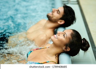 Happy couple leaning their heads at the edge of a pool while relaxing in thermal water at the spa.