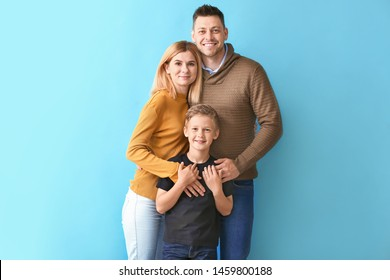 Happy couple with little adopted boy on color background