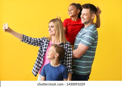 Happy couple with little adopted children taking selfie on color background