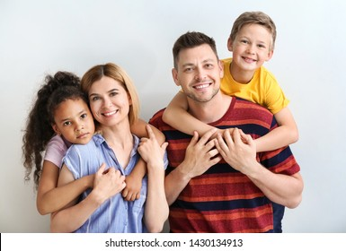 Happy couple with little adopted children on light background