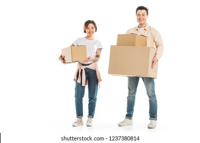 happy couple looking at camera and holding cardboard boxes isolated on white, moving to new house concept