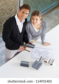 Happy couple looking at different window profiles for home renovation