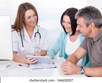 Happy Couple Looking At Digital Tablet Held By Doctor