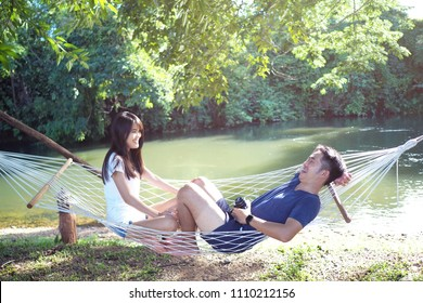 Happy couple looking each other laughing sitting on hammock, soft focus.