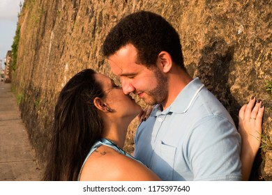 a happy couple looking at each other on the wall of a street