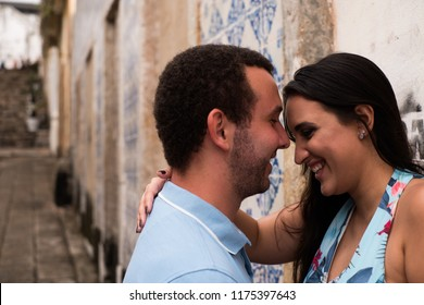 a happy couple looking at each other on the wall of a street and hand in the hair