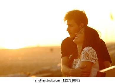 Happy couple in love dating and flirting at sunset sitting on a bench on the beach