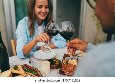 Happy couple in love dating at home terrace drinking red wine, laughing, joking and making cheers during eating, girl on a first date embarrassed clinks a glass with her boyfriend, People Celebrate