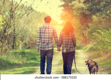 Happy couple in love with dog walking on rural dirt road in springtime at sunset. Woman and man holding hands. Woman keeps her dog on a leash. Couple and dog back to camera. Casual stile.