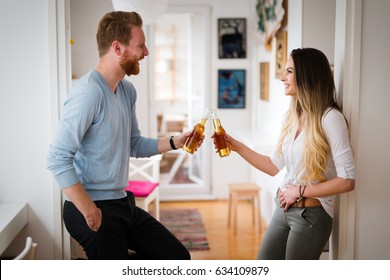 Happy couple in love drinking beer and toasting at home