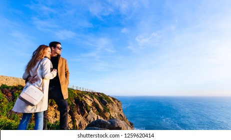 happy couple in love embracing each other on a high rocky shore and looking at the evening ocean