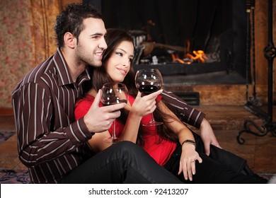 Happy couple in love enjoying wine near fireplace