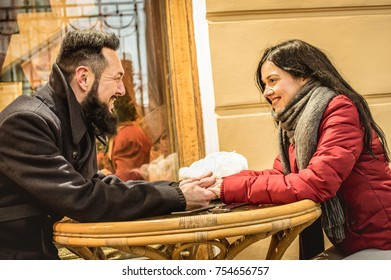 Happy couple in love enjoying winter time at restaurant bar outdoor - Handsome hipster man with young woman talking and holding hand - Relationship concept with boyfriend and girlfriend on warm filter