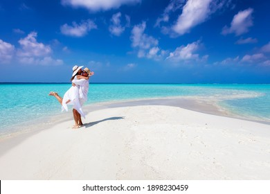 Happy couple in love is having fun and hugging on a sandbar with white sand and turquoise ocean - Shutterstock ID 1898230459