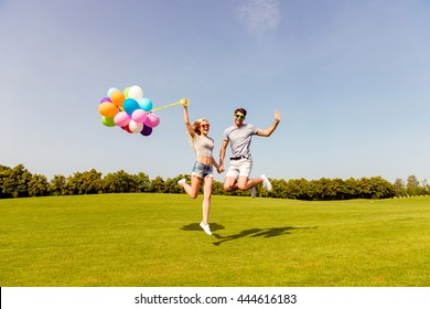 Happy couple in love having fun and jumping with balloons