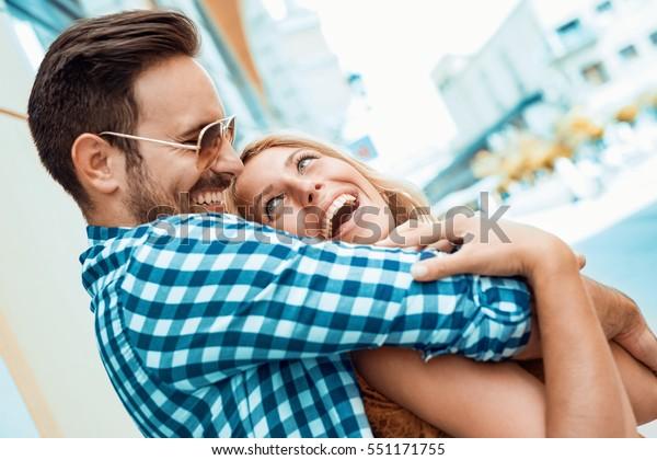 Счастливая пара в любви весело на открытом воздухе и улыбается.