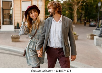 Happy couple in love having a rest in city at sunny day. Spring stylish elegant clothes. Blond woman in hat holding hand her handsome husband with beard in suit.