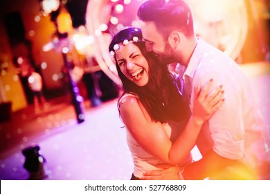 Happy couple in love hugging and smiling at festival