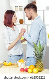 happy couple in love in kitchen making healthy juice from fresh orange