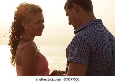 Happy Couple in love on dating Man and woman embracing and watching sea sunset. Beautiful Young  man and his girlfriend near sea. Man and woman talking and hugging. Boyfriend and girlfriend.