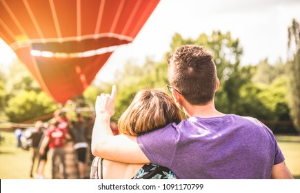 Happy couple in love on honeymoon excursion waiting for hot air balloon ride - Summer travel concept with young people travelers having fun at trip vacation - Bright warm filter with backlight