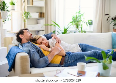 Happy couple in love on sofa indoors at home, sleeping.