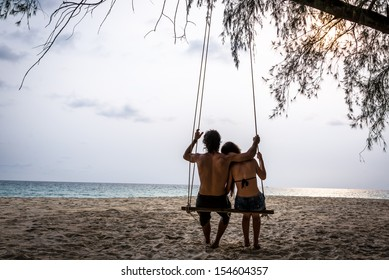 Happy Couple in Love on a Swing looking at the ocean. Koh Kood Island, South East Asia. Thailand.