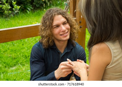 Happy couple in love at outdoors and looking at each other, man on his knees and holding her girlfriend hands, proposing to marry him, in a patio backyard background