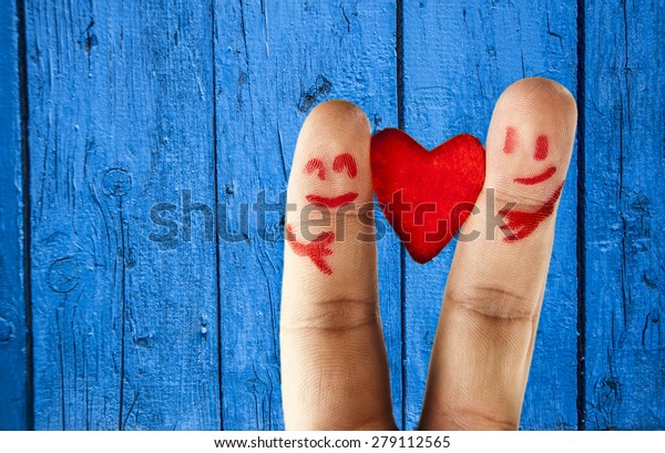 happy couple in love with painted smiley and hugging One red heart between two finger in form of lovely people face with hand hold sign of peace, friendship Symbol Valentin's Day on wooden background