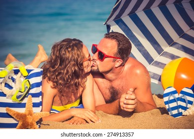 Happy couple in love. People lying on the beach. Young man and woman kissing. Summer vacation concept