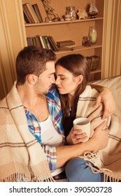 Happy couple in love with plaid and cup embracing each other