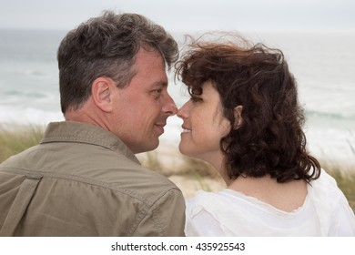 Happy couple in love relaxing on beach vacation enjoying ocean view together sitting in the sand embracing and hugging.