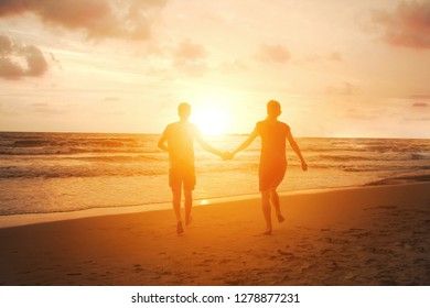Happy couple in love run to sun on sea beach. Harmony relationship. Family vacation travel to tropical country. Beautiful sunset view. Honeymoon in Thailand.