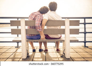 happy couple in love  in Santa monica sitting on a bench. People and relationship concept