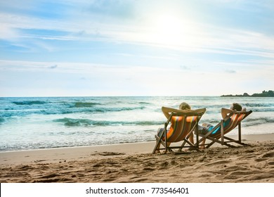 Happy couple in love sitting in deck chairs on luxury sunset sea beach in Thailand. Romantic honeymoon vacation in tropical country.