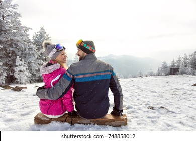 Happy couple in love sitting on ski terrain at winter holiday