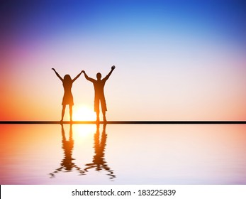A happy couple in love standing together with hands raised at sunset with water reflection