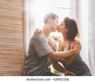 Happy couple in love. Stunning sensual portrait of young stylish fashion couple in bedroom. Young man and woman kissing.