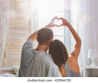 Happy couple in love. Stunning sensual portrait of young stylish fashion couple in bedroom.