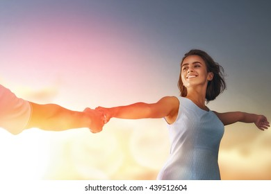 Happy couple in love. Stunning sensual portrait of young stylish fashion couple outdoors. Young woman holds the hand of her boyfriend on background sunset sky.