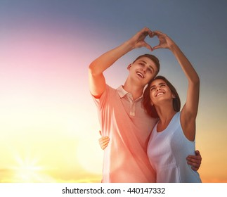 Happy couple in love. Stunning sensual portrait of young stylish fashion couple outdoors. Young man and woman on background sunset sky.