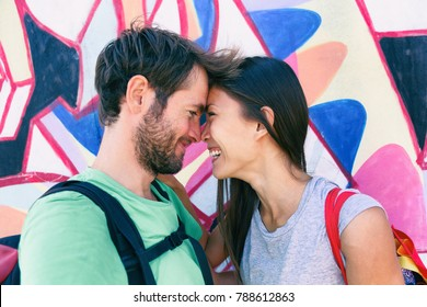 Happy couple in love taking a selfie doing funny kissing pose at famous tourist attraction Berlin wall, Germany, Europe travel destination. Laughing interracial young people tourists.