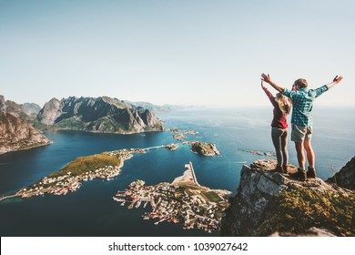 Happy Couple love and travel raised hands on cliff in Norway man and woman family travelers lifestyle concept summer vacations outdoor Lofoten islands