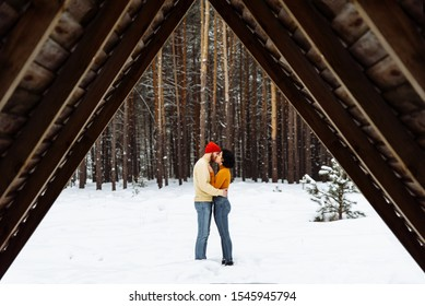 Happy couple in love walks in the winter forest. Theу kisses and hugging each other with love