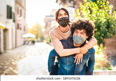 Happy couple of lovers enjoying time outdoor at Valentines day - Handsome guy with nice girl on piggy back moment - New normal love concept with boyfriend and girlfriend together on warm vivid filter